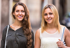 Two cheerful girls walking in city Stock Images