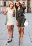 Two cheerful girls walking in city Royalty Free Stock Photos