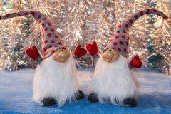 Two cheerful gnomes with hands up facing each other on a silver Stock Images