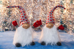 Two cheerful gnomes with  hands up on silver tinsel background Royalty Free Stock Photos