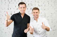 Two cheerful guys. Two attractive guys in the studio. Business and education stock photography