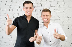 Two cheerful guys. Two attractive guys in the studio. Business and education stock photo