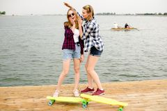 Two cheerful happy skater girls in hipster outfit having fun on a wooden pier during summer vacation stock photo