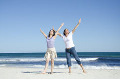 Two cheerful happy women at the beach. Two generations, two women, mother and daughter are happy together at the beach, in a cheerful mood with their arms up in Stock Images