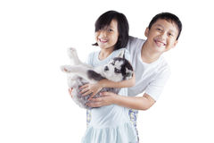 Two cheerful kids and husky puppy Royalty Free Stock Images