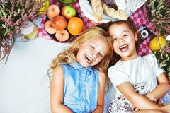 Two cheerful kids lying on a picnic blanket among refreshments. Two cheerful children lying on a picnic blanket among refreshments royalty free stock photography