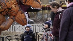 Two cheerful kids talking to person in t rex costume at sidewalk. Two cheerful caucasian kids talking to person in t rex costume at sidewalk. Cold sunny spring stock video footage