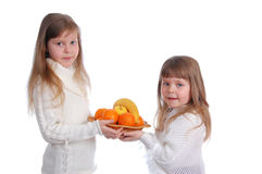 Two cheerful little girls with fruits. Two cheerful little girls with fruit on the white royalty free stock photos