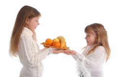 Two cheerful little girls with fruits. Two cheerful little girls with fruit on the white stock image