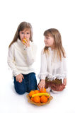 Two cheerful little girls with fruits. Two cheerful little girls with fruit on the white Royalty Free Stock Image