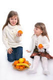 Two cheerful little girls with fruits Royalty Free Stock Photography
