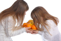 Two cheerful little girls looks at fruit. On the white royalty free stock photo