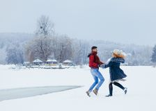 Two cheerful lovers are holding hands and joyfully dancing on the snow in the countryside. Christmas time. Stock Photography