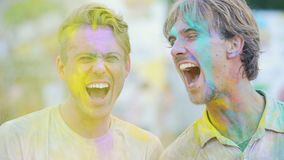 Two cheerful male friends having fun at outdoor color festival, giving high five. Stock footage stock footage