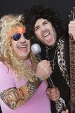 Two cheerful male friends singing and playing guitar Royalty Free Stock Photography