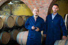 Two cheerful men in uniforms standing in cellar with wine woods Royalty Free Stock Image