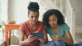Two cheerful mixed race curly women shopping online with tablet computer and credit card at home stock footage