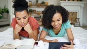 Two cheerful mixed race funny girlfriends reading book and using tablet computer talks and have fun lying in bed at home. Two cheerful mixed race funny Royalty Free Stock Photography