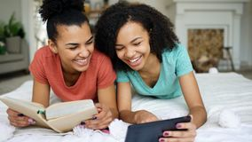 Two cheerful mixed race funny girlfriends reading book and using tablet computer talks and have fun lying in bed at home. Two cheerful mixed race funny Royalty Free Stock Images