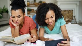 Two cheerful mixed race funny girlfriends reading book and using tablet computer talks and have fun lying in bed at home. Two cheerful mixed race funny Stock Photos