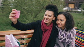 Two cheerful mixed race woman with shopping bags talking at video call with smartpone. Young girls sitting on bench have stock video footage