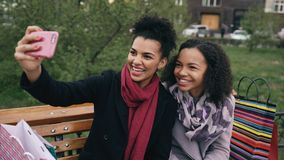 Two cheerful mixed race woman with shopping bags talking at video call with smartpone. Young girls sitting on bench have. Two cheerful mixed race women with royalty free stock photos