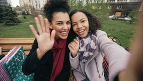 Two cheerful mixed race woman with shopping bags talking at video call with smartpone. Young girls sitting on bench have stock photos