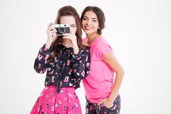 Two cheerful pretty young women taking pictures with vintage camera Stock Image