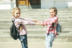 Two cheerful schoolgirls with schoolbags Royalty Free Stock Images