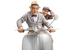 Two cheerful senior men riding a scooter. Isolated on white background royalty free stock photography