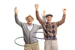 Two cheerful senior men spininng hula hoops. Isolated on white background royalty free stock photography