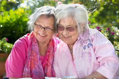 Two smiling senior woman relaxing in garden Royalty Free Stock Image