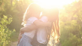 Two cheerful sisters hug. Two cheerful sisters. Cute girl hugging in the park at sunset. Family values stock video