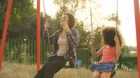 Two cheerful sisters moving back and forth on swings, outdoor child playground. Stock footage stock video