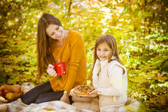 Two cheerful sisters in the park in warm autumn day Stock Images