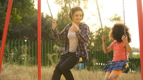 Two cheerful sisters swinging together at outdoor child playground, happiness royalty free stock image