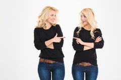 Two cheerful sisters twins pointing and looking at each other Stock Photos
