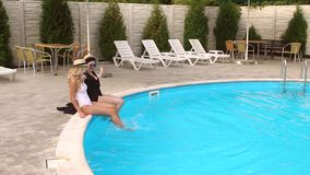 Two girls Teens having fun in the pool on vacation. Two cheerful slim girls teenagers have fun in the pool, their feet creating splashes, slow motion stock video