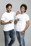 Two cheerful smart young male smiling with cup of coffee. On grey background Stock Photos