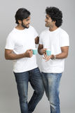 Two cheerful smart young male standing and chatting with cup of coffee. On grey background royalty free stock photo