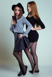 Two cheerful smiling sexy girl girlfriends photographed on the phone, do selfie phone in the studio on a gray background Stock Images