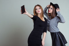 Two cheerful smiling sexy girl girlfriends photographed on the phone, do selfie phone in the studio on a gray background Royalty Free Stock Image