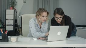 Two cheerful smiling young business women working on laptop royalty free stock photography