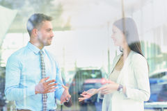 Two cheerful smiling young businesspeople talking at the office. View through window Stock Image