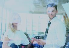 Two cheerful smiling young businesspeople talking at the office. View through window. Two cheerful smiling young businesspeople talking at the office. View Stock Image