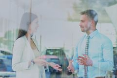 Two cheerful smiling young businesspeople talking at the office. View through window. Stock Photos