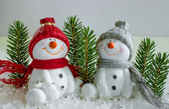 Two cheerful snowman in the snow celebrate the New Year. Stock Photography