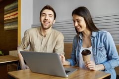 Two cheerful students with dark hair sitting in cafeteria, drinking coffee and laughing, looking video from yesterday`s Stock Image