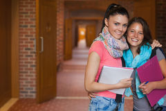 Two cheerful students posing in hallway Stock Photos