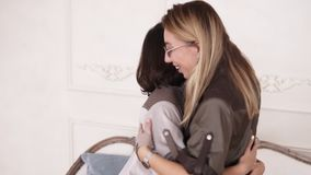 Two cheerful stylish girls happy to see each other. Girl friends hugging each other and jumping on sofa.  stock video